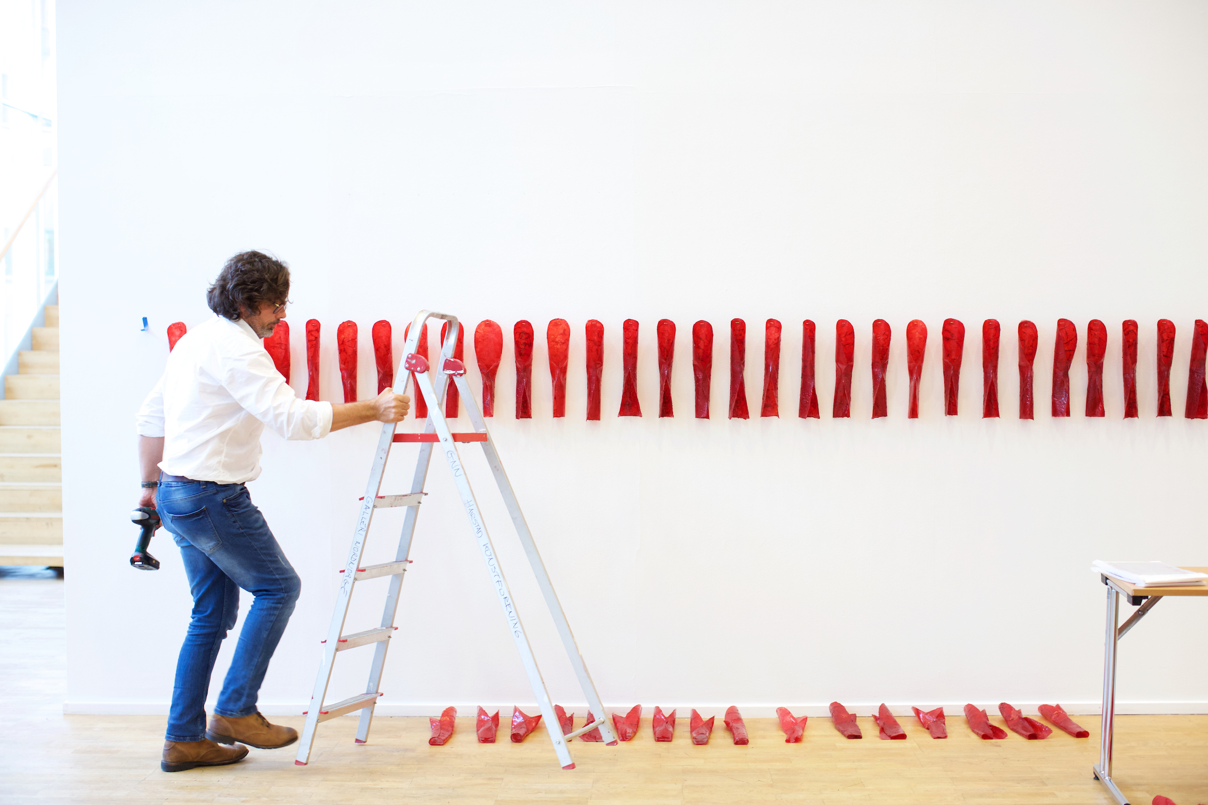 "Artist Marek Ranis helps install ""Red Curl"" by Sonya Kellhier-Coombs."